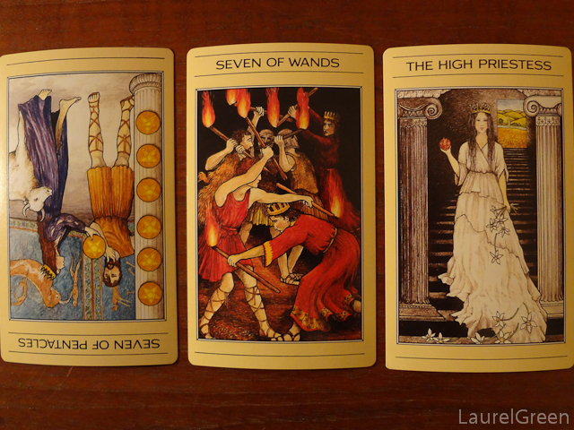 a three card tarot spread with the seven of pentacles reversed, the seven of wands and the high priestess