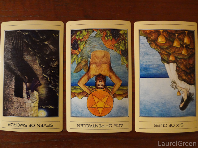 a three card tarot spread with the seven of swords reversed, the ace of pentacles reversed and the six of cups reversed