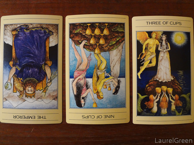 a three card tarot spread with the emperor reversed, the nine of cups reversed and the three of cups