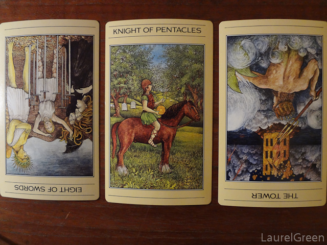 a three card tarot spread with the eight of swords reversed, the knight of pentacles and the tower reversed