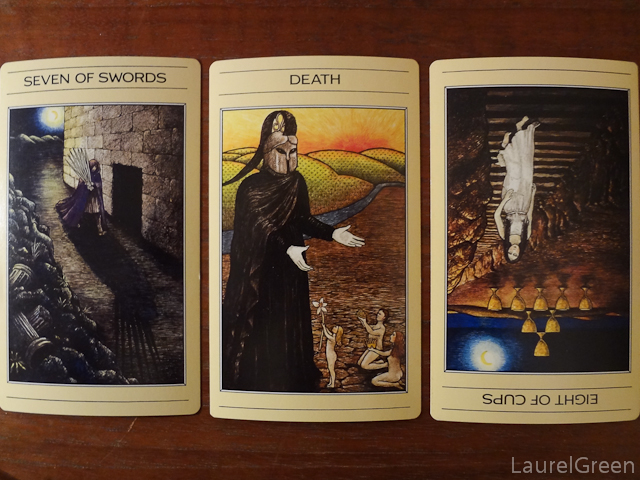 a three card tarot spread wit the seven of swords, death and the eight of cups reversed