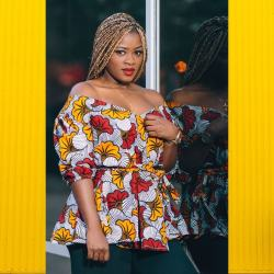 Pretty African Lady wearing golden braids and a patterened african print off shoulder blouse.