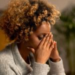 Young african lady with brown curly hair - head in hands - worrying about my health