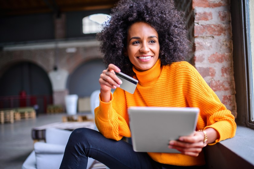 Photo of woman sitting by window smiling with a credit card and tablet