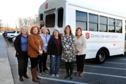 Photo of home office employees posing in front of a Salvation Army truck