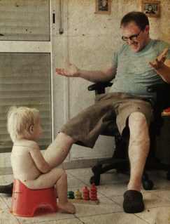 Child on potty play with father. Photo in old image style.