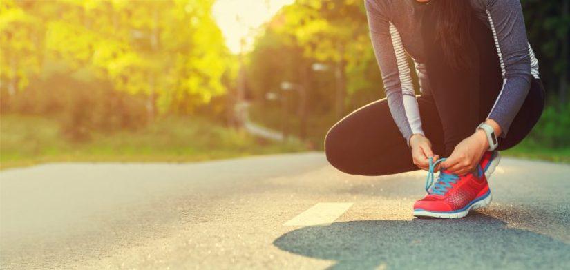 Female runner tying her shoes preparing for a run a jog outside