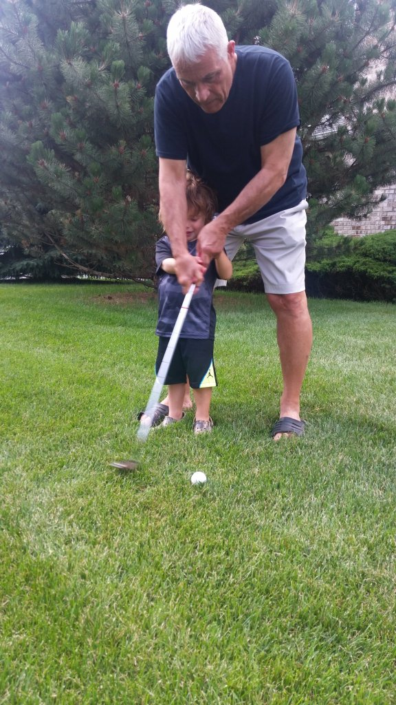 Raynold T. Petrocelli teaching his grandson to golf