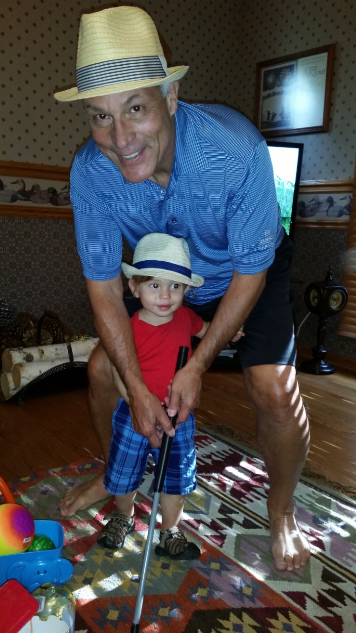 Raynold T. Petrocelli playing golf with his grandson