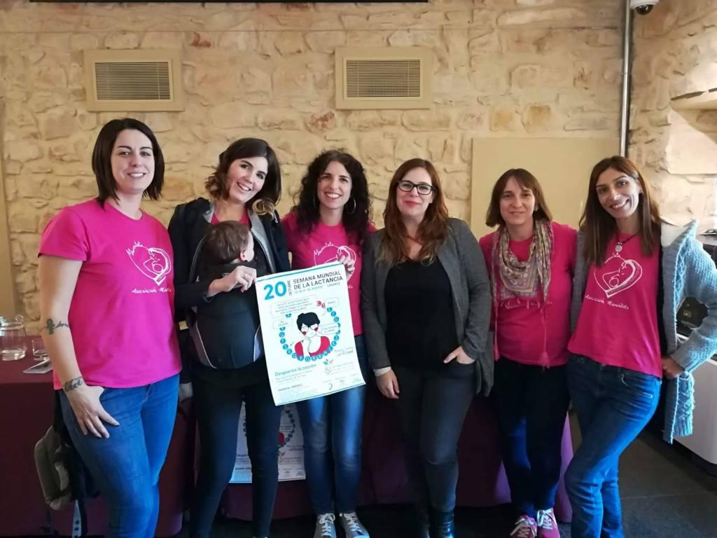 Foto de 6 mujeres, integrantes del asociacion de apoyo a la lactancia mamateta y Mamen Jimenez La Psicomami, sujentando el cartel del evento Despierta tu pasión