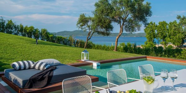 Picture showing outdoor dining table, sun lounger, pool, garden and seaviews from Villa Ostraco IV, part of Seafront luxury Villa Ostraco IV is part of a luxurious villa complex located in peaceful Mount Athos Area, Halkidiki,