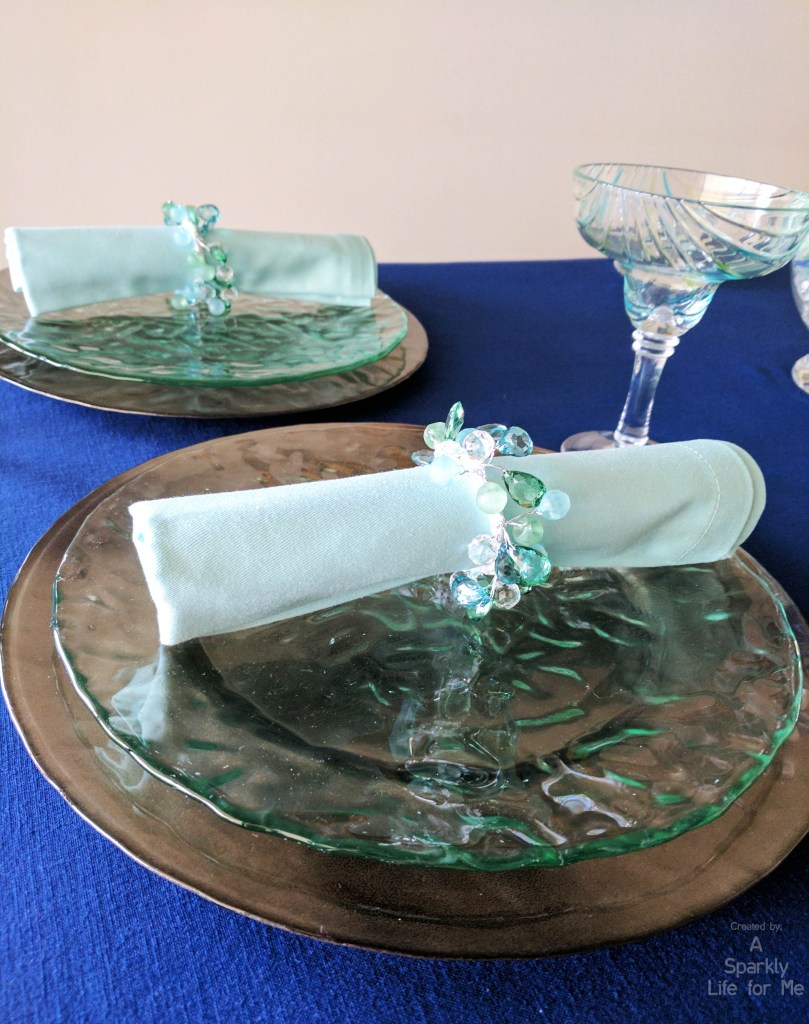 Double Charger Place Settings with Rolled Napkin Folds and Sea Glass Napkin Rings