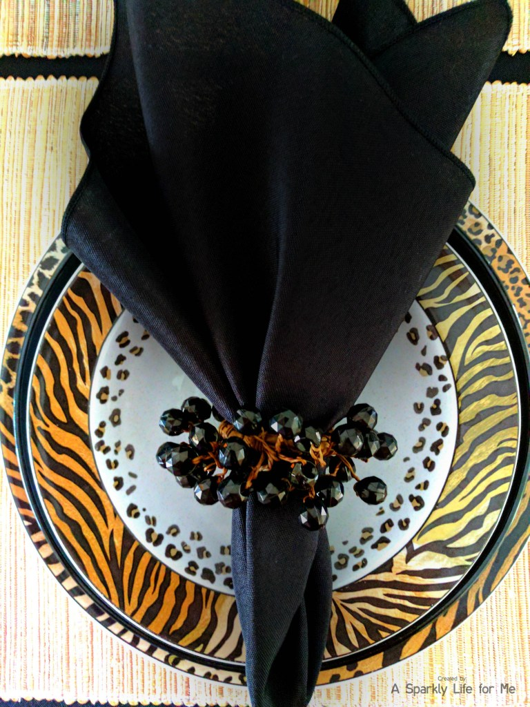Jungle animal print place setting in black with leopard and tiger prints with black napkins