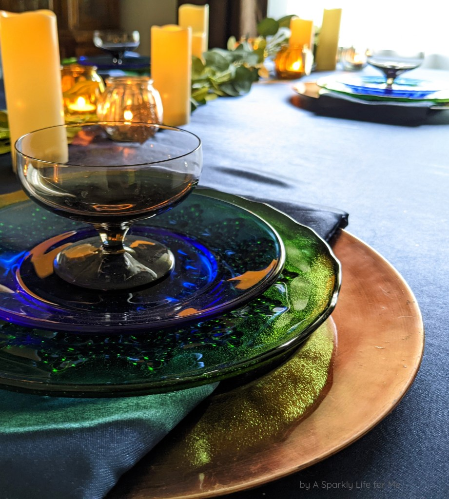 Layered Place Setting with Cobalt Glass Plate, Textured Green Plates, Smoky Grey Glass, and Copper Charger with Navy Satin Napkin