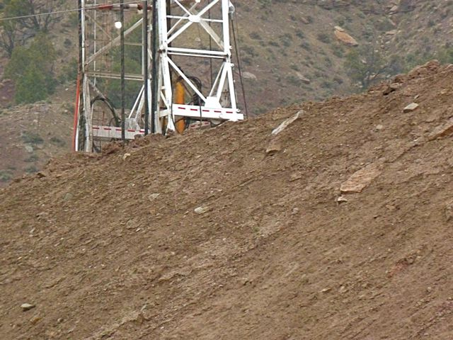 A rig behind an open dirt wall north of Parachute.