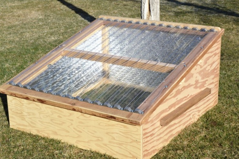 """Before starting on a greenhouse, the (co)studio class built a number of """"cold frames,"""" miniature greenhouses that enable gardeners to protect young plants from early-season frosts. By selling the cold frames, the class is raising the cash to buy the greenhouse materials."""