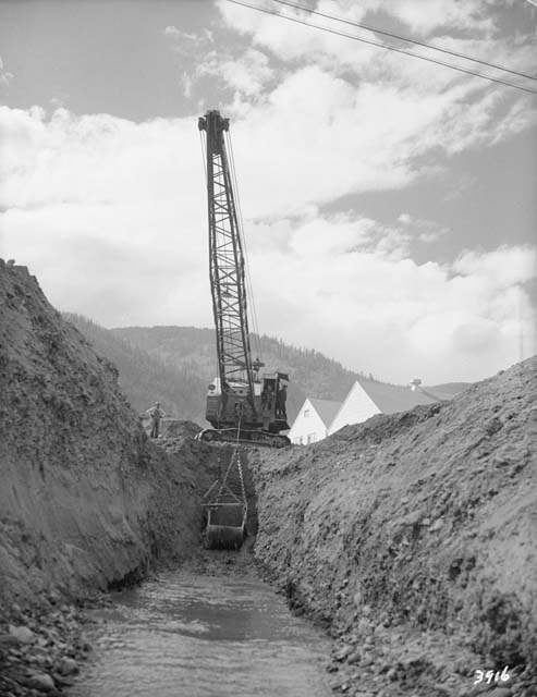 A crane digging a channel at Camp Hale to hold water from the Eagle River.