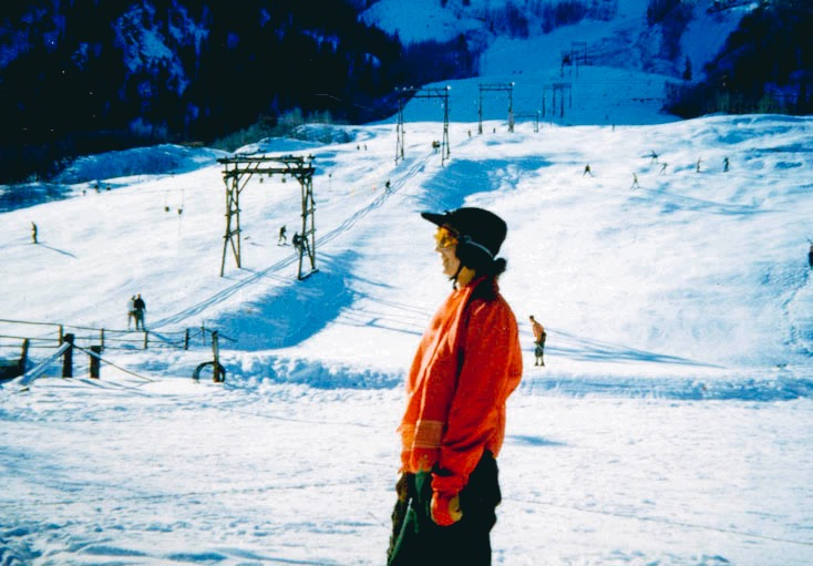 A woman in haute ski gear standing at the bottom of the Little Nell Constam T-bar in 1952, which ran up Nell from 1948-1956, when it was replaced by the old Lift-4. Visible above the top of the T-bar is what is now upper Little Nell, which was then called the bottom of the Silver Queen trail.