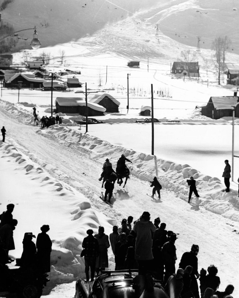 Two skiers being pulled by horses (ski joring) in the street along Mill Street near Wagner Park, 1955. Ski joring was one of many annual Winterskol skiing events into the mid-1980s. The original Lift-1 is in the background.