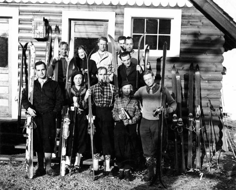 Before there were any ski lifts in Aspen, a group of hearty, guided, hike-to-ski skiers at the Highlands Bavarian Lodge in 1936—located near the intersection of Castle Creek and Conundrum Road—pose for a group photo. Judging by the spring-like snow on their skis and the eastern-facing late-afternoon shadows, they likely just finished a ski run—quite possibly down Mt. Hayden, which was then being considered for development into a ski area, along with a European-style gondola. Three men in the front are wearing ties. Pictured in the top row are Andre Roch, Gretl Arnold Fuler, Steve Hart, Norman Barwise, and an unknown person. In the bottom row are William V. Hodges, Martha Wilcox, Joseph Hodges, Polly Grimes, and Frank Ashley.
