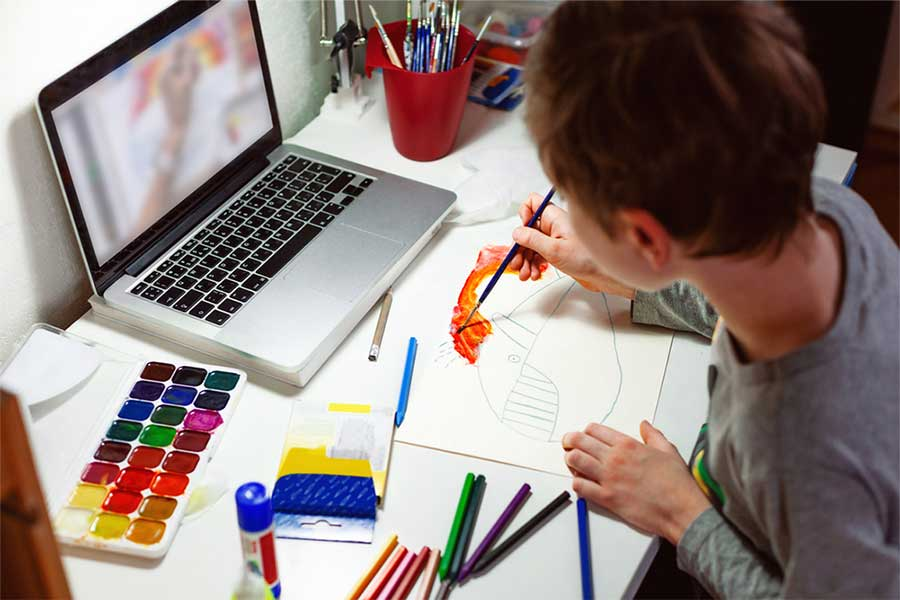 A student paints a whale during an online lesson