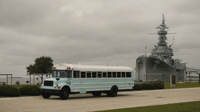 Skoolie parked in front of the USS Alabama.