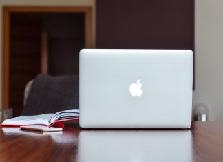 An Apple Macbook kept on a brown table