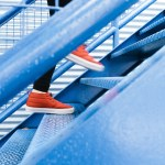 A person climbing blue stairs | Aspioneer