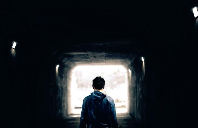 A millennial standing in an alley