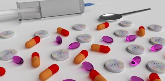 A number of colorful looking drug pills next to injection needle