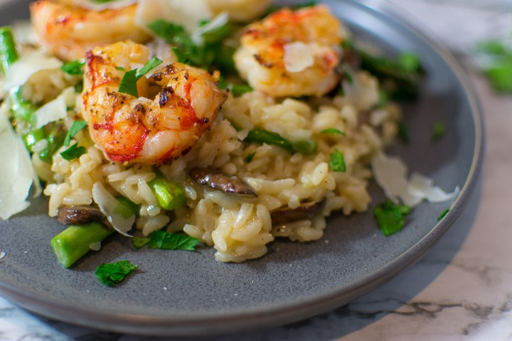 Closeup of risotto on a plate with shrimp and asparagus and mushrooms