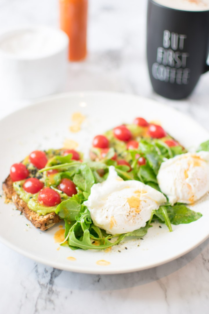 Spicy Avocado Toast on a plate with two poached eggs and arugula