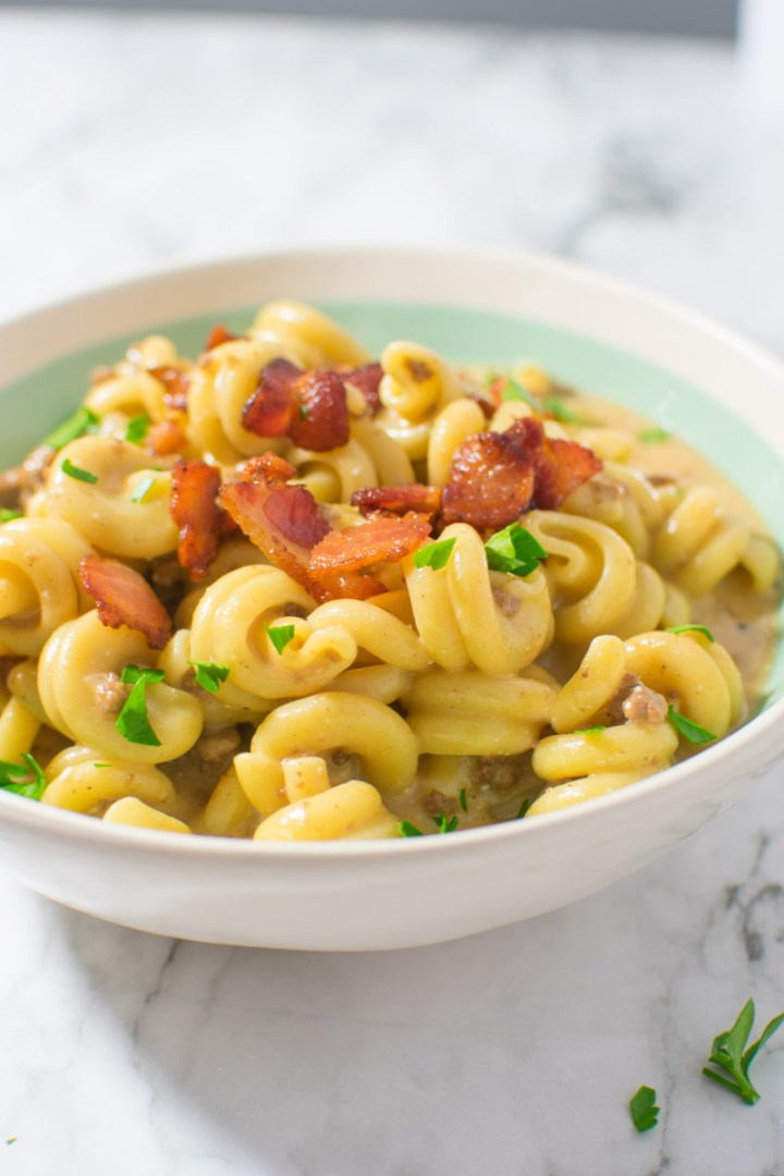 Instant Pot Bacon Cheeseburger Pasta in bowl with bacon on top