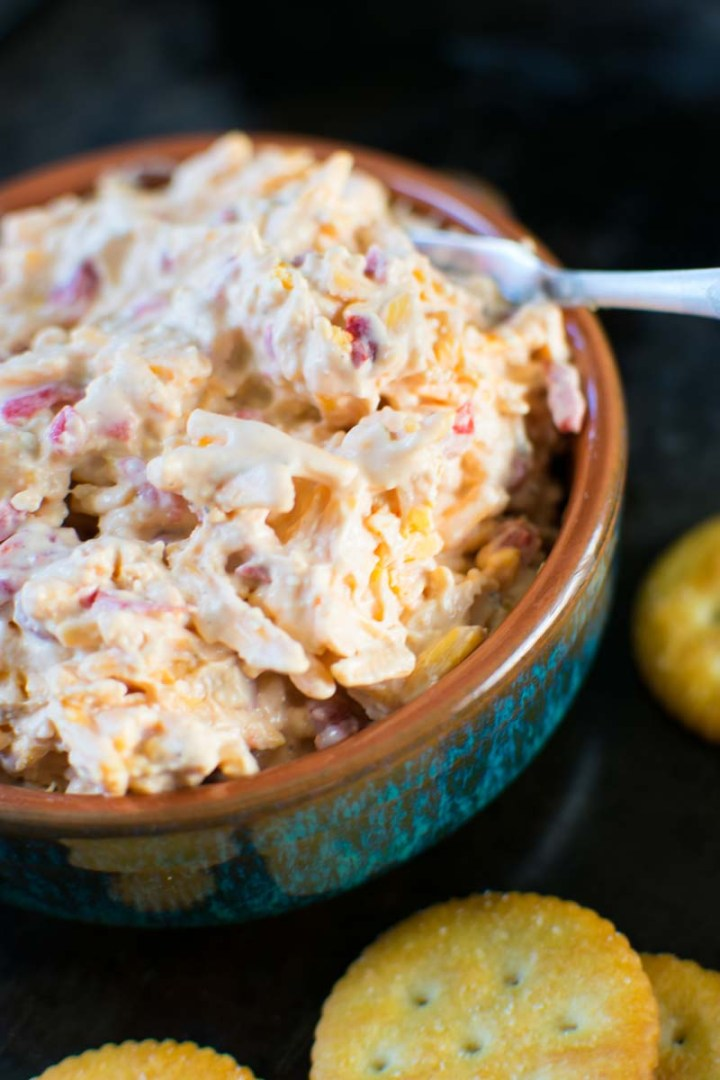 Quick Homemade Southern Pimiento Cheese in bowl, closeup view with crackers on a plate