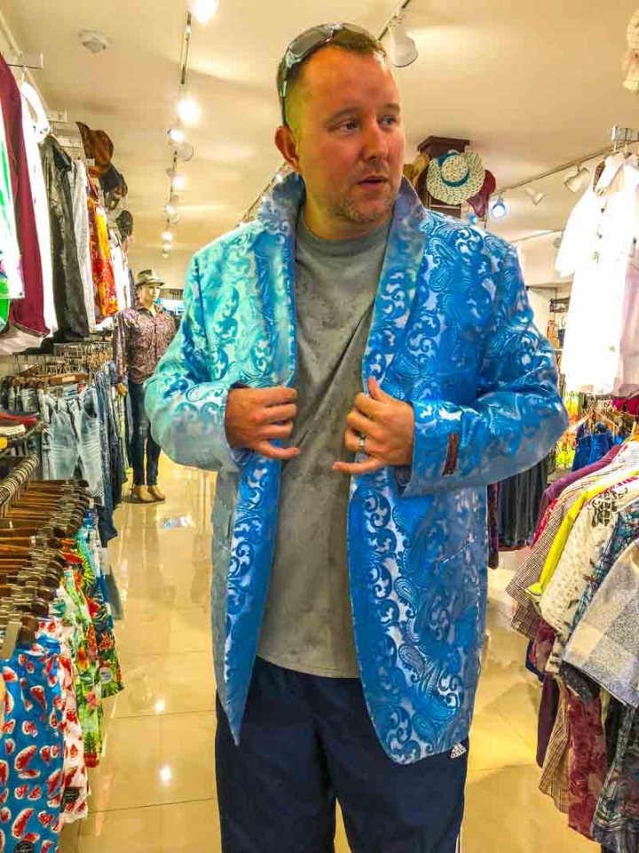 The husband trying on a shiny blue jacket