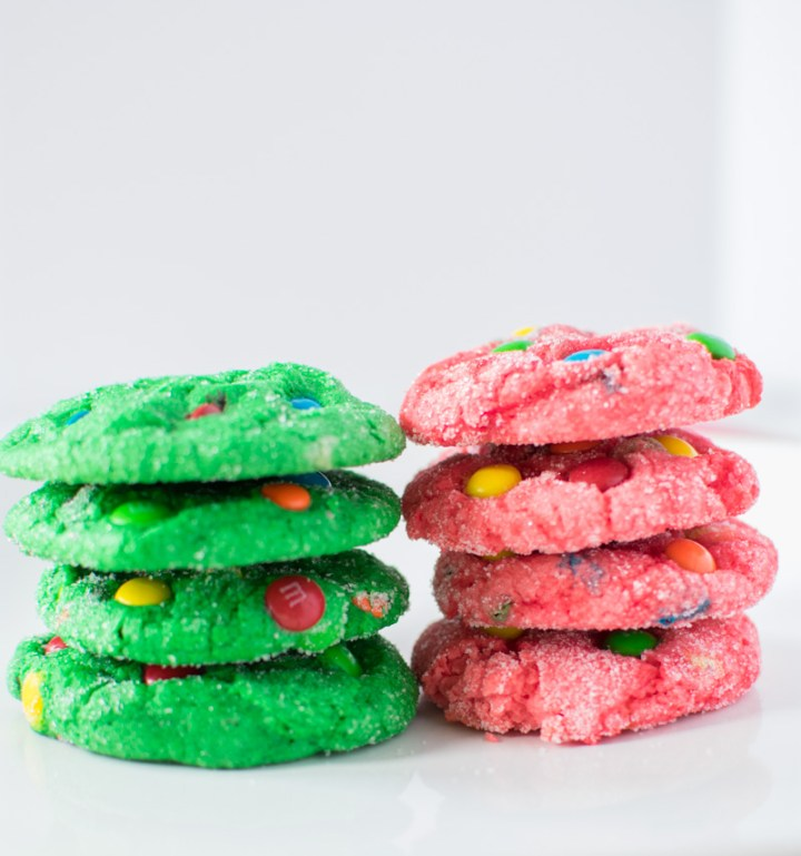 4 green and 4 red M&M Crinkle Christmas Cookies stacked on plate
