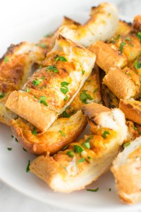 Close up of slices of Cheesy Ranch Garlic Bread on a plate