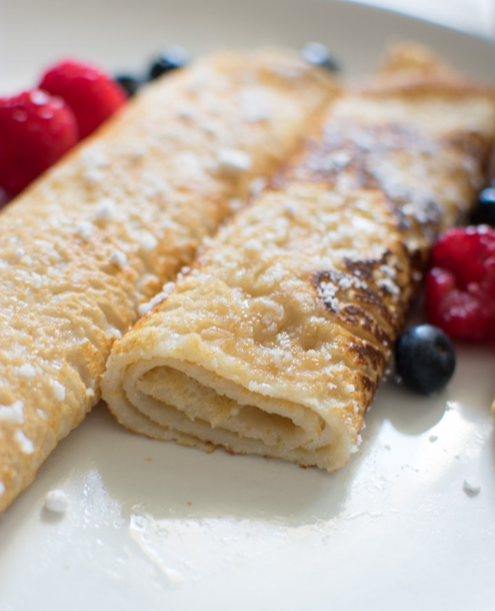 Closeup of crepes on a plate with a bite taken out of it