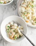 Overhead picture of Gnocchi with Gorgonzola Cream sauce in a small serving bowl with the corner of a large serving bowl