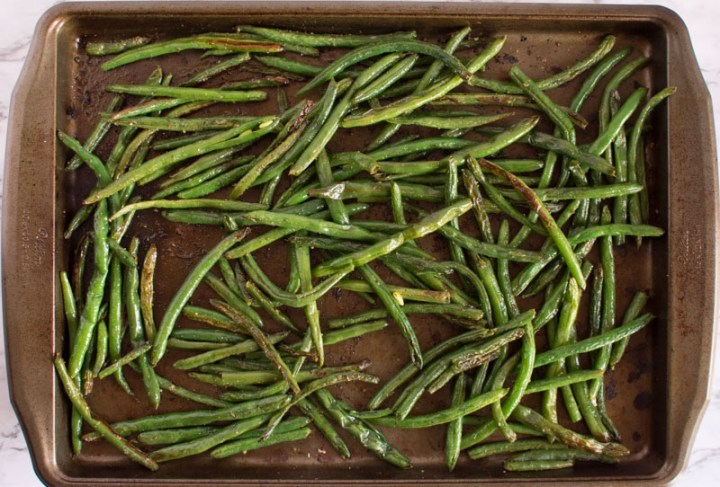 Overhead view of crispy browned beans on a baking sheet