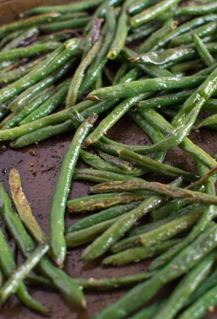Crispy, browned roasted green beans on a baking sheet