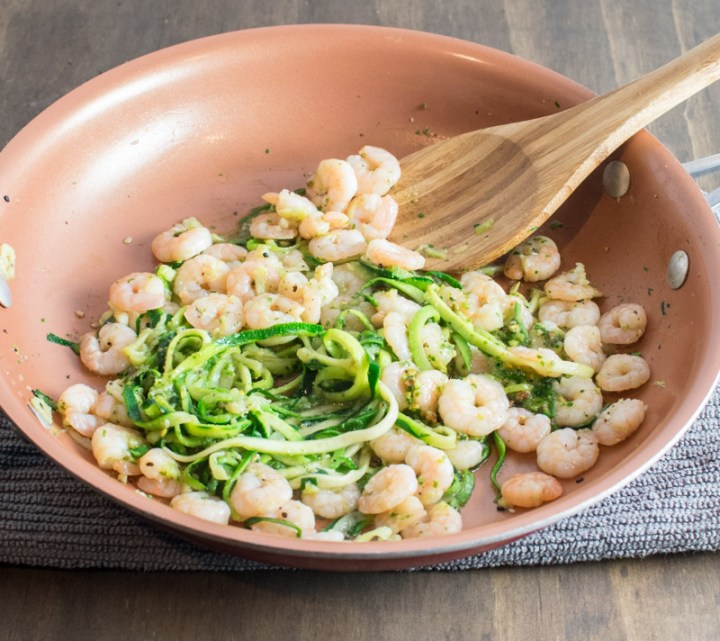 Adding pesto to shrimp and zoodles in a skillet