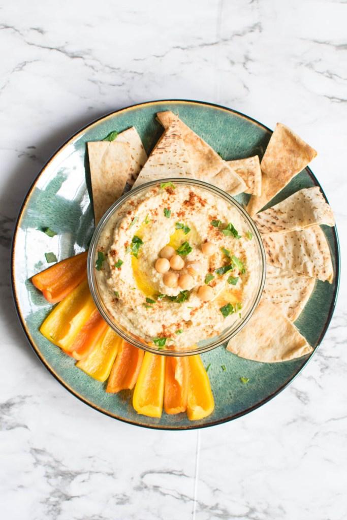 Overhead view of hummus, veggies and pita chips