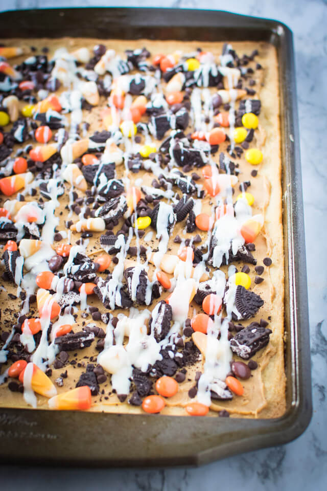 Cream cheese frosting drizzled on top of Halloween Sugar Cookie Pizza