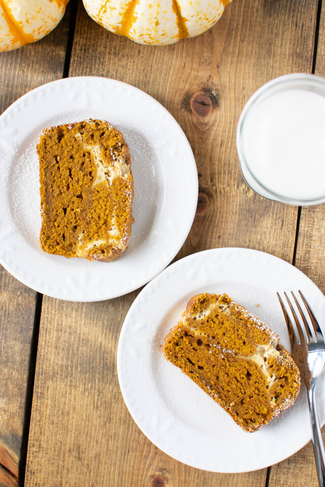 Overhead view of two slices of pumpkin cheesecake bread on plates
