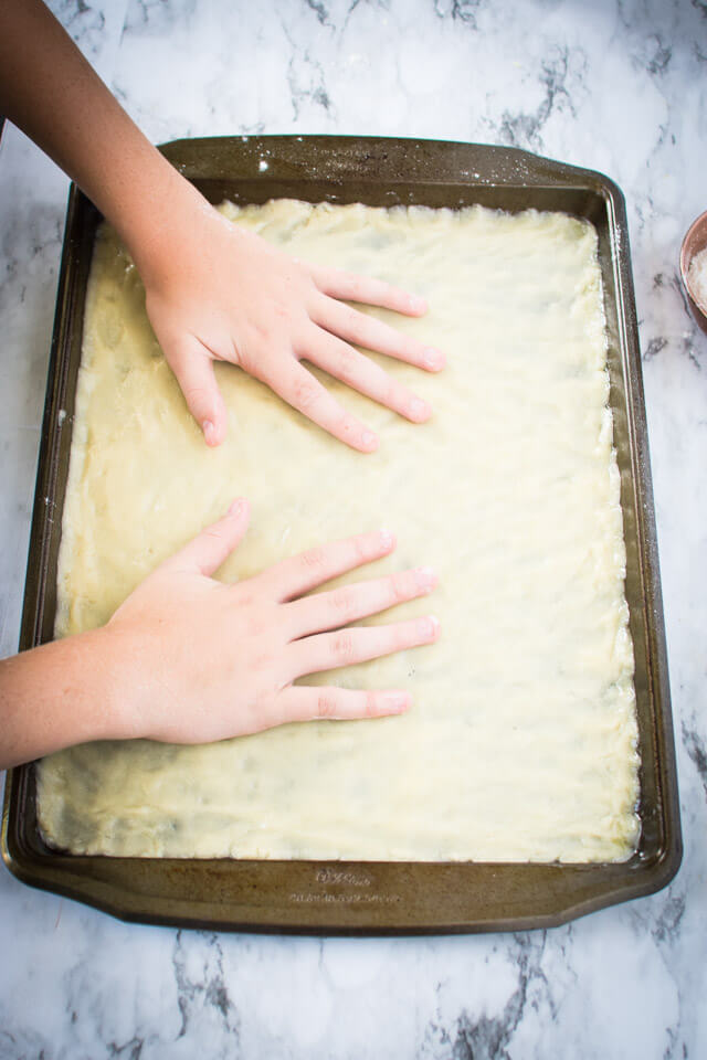 Spreading cookie dough in baking sheet pan