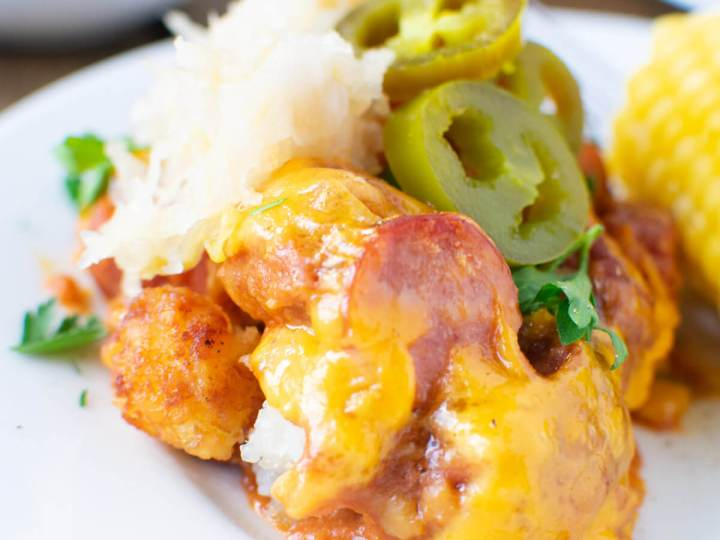 Chili Dog Tater Tot Casserole serving on a plate topped with sauerkraut and jalapeños