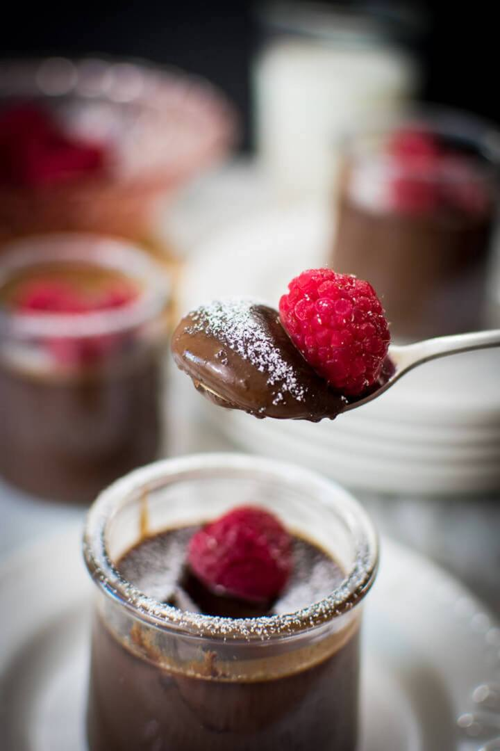 Closeup of a spoonful of chocolate dessert with a raspberry on top, sprinkled with powdered sugar.