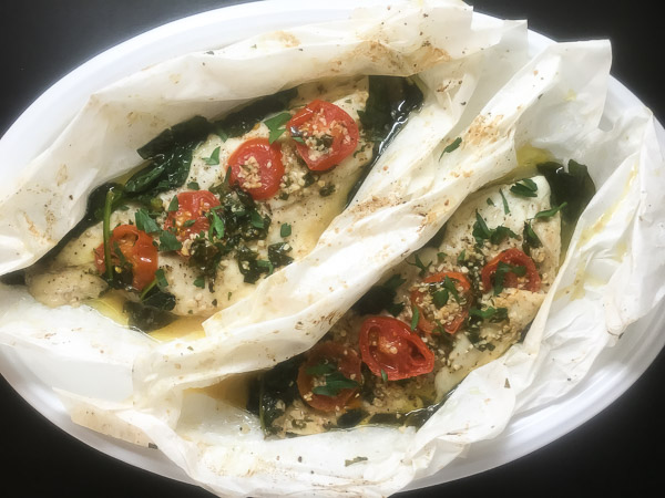 Cajun RedFish En Papillote with Creole garlic sauce, spinach and tomatoes.