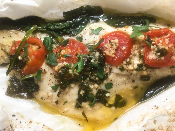 Louisiana Redfish in Papillote in parchment paper with Creole garlic sauce, tomatoes and spinach.